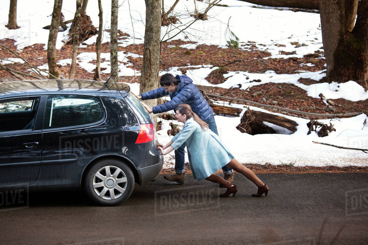 couple pushing car in forest stock photo dissolve