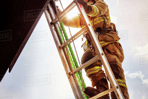 Firefighter climbing ladder Royalty-free stock photo