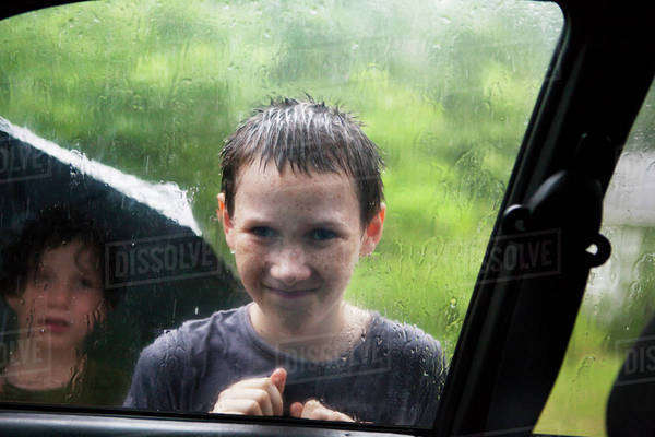 Two boys (10-11, 6-7) looking through car window in rain Royalty-free stock photo