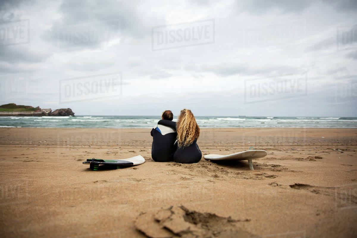 Rear view of couple sitting with surfboards at beach against sky Royalty-free stock photo