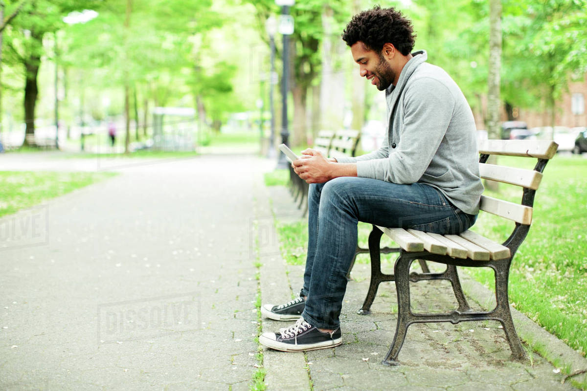 Side View Of Happy Man Using Smart Phone While Sitting On Park Bench By Footpath Stock Photo