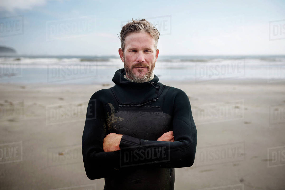 Portrait of mature surfer standing with arms crossed at beach Royalty-free stock photo