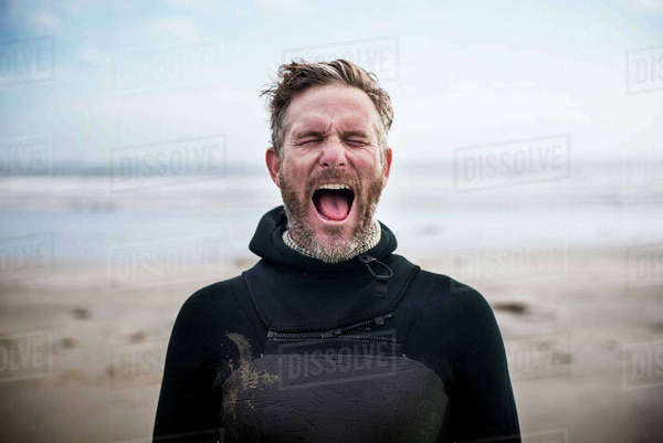 Male surfer screaming while standing at beach Royalty-free stock photo