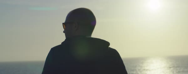 Rear view of man looking at sea view against sky during sunset Royalty-free stock video