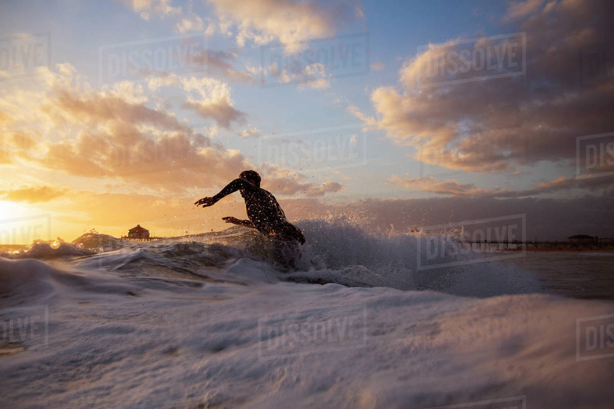 4721a96025 Man surfing on waves against sky during sunset - Stock Photo - Dissolve