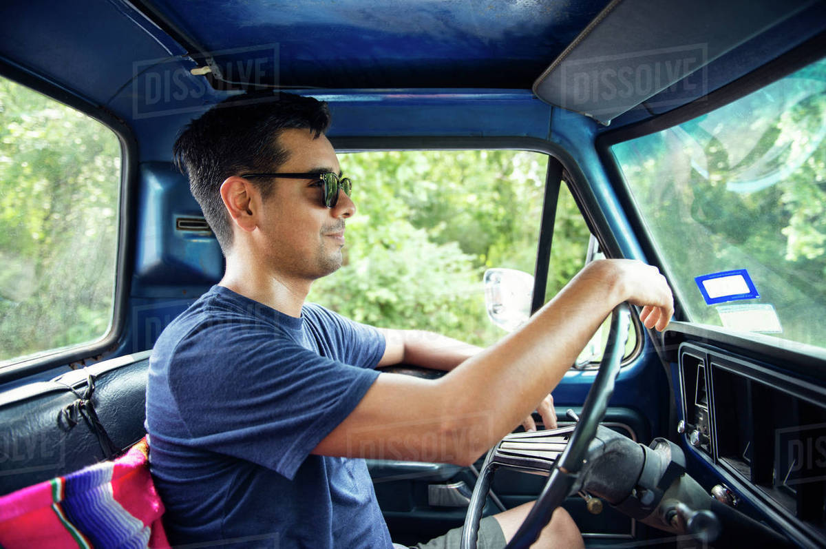 8d87ddb39c Man in sunglasses driving pick-up truck - Stock Photo - Dissolve