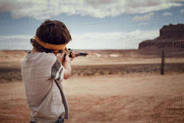 Boy aiming rifle while standing on field against sky Royalty-free stock photo