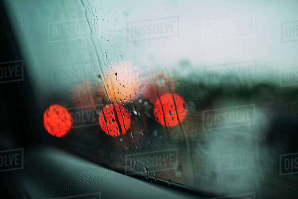 Defocused lights seen through wet car window in rainy season Royalty-free stock photo