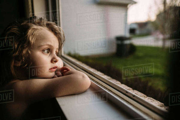 Thoughtful girl looking away while leaning on window sill Royalty-free stock photo