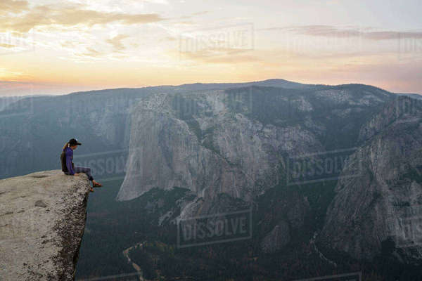 Side view of woman sitting on cliff during sunset Royalty-free stock photo