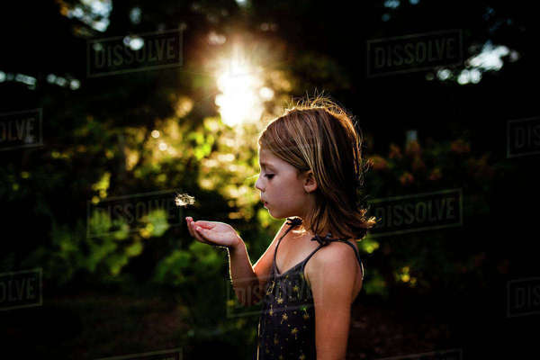 Side view of girl blowing dandelion seed while standing at yard Royalty-free stock photo