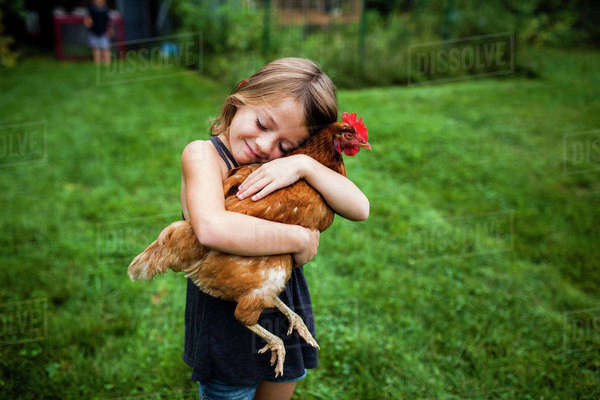 Smiling girl with eyes closed holding hen while standing in yard Royalty-free stock photo