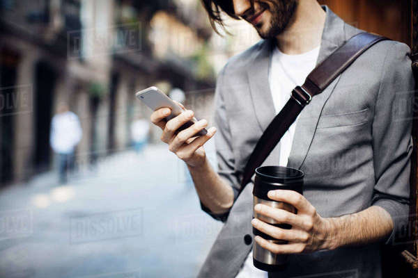 Businessman with drink using mobile phone in city Royalty-free stock photo
