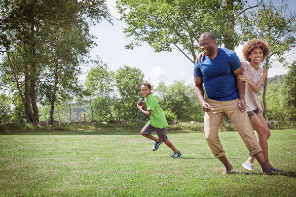 Father playing american football with his children (8-9, 14-15) Royalty-free stock photo