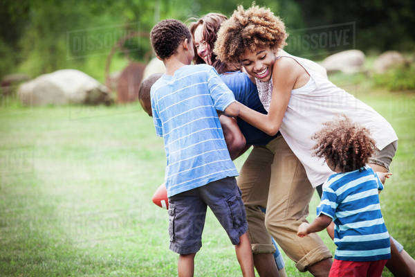 Parents playing american football with their children (2-3, 8-9, 14-15) Royalty-free stock photo