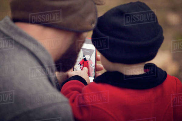 Rear view of father and baby girl (18-23 months) looking at picture on smart phone Royalty-free stock photo