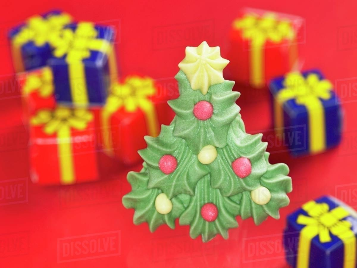A Sugar Christmas Tree With Presents In The Background Stock Photo
