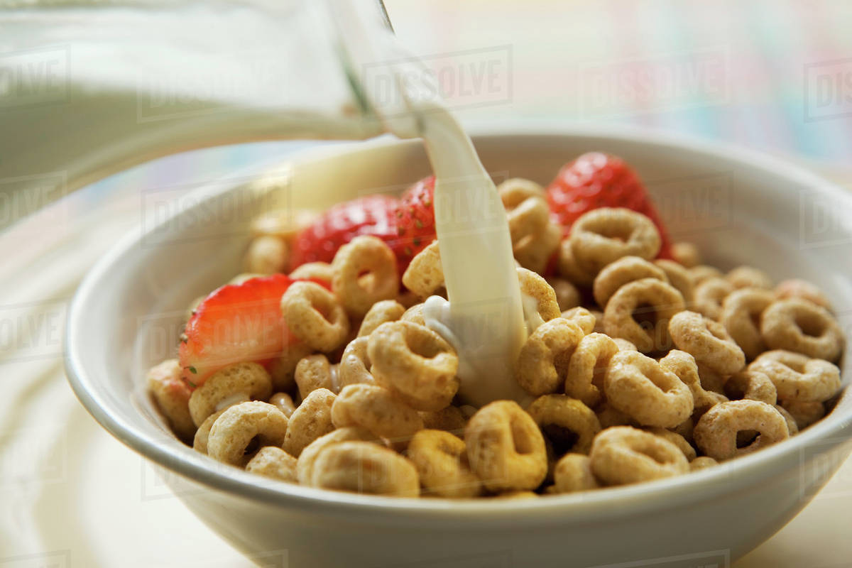 Pouring milk over cereal in a bowl - Stock Photo - Dissolve