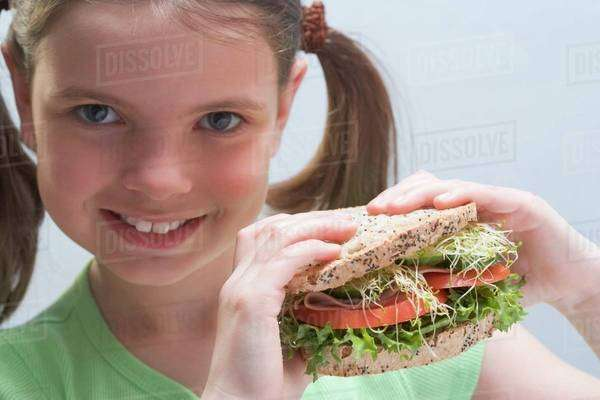 Smiling girl holding a sandwich Royalty-free stock photo