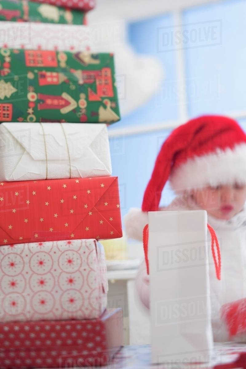 A pile of Christmas gifts, child in Father Christmas hat - Stock ...