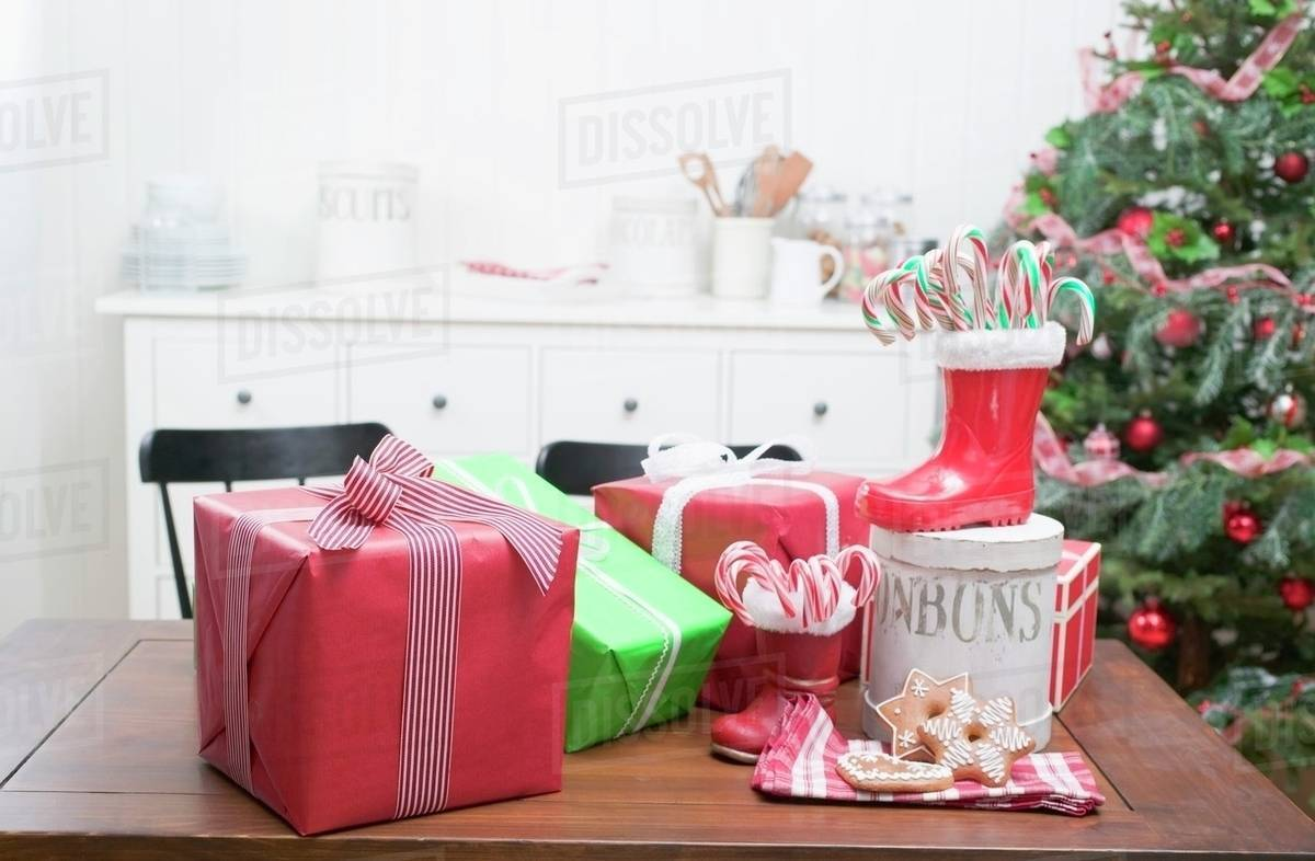 Christmas gifts, candy canes, gingerbread on kitchen table - Stock ...