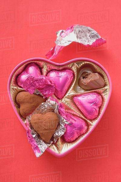 Pink chocolates in heart-shaped box (one partly eaten) Royalty-free stock photo