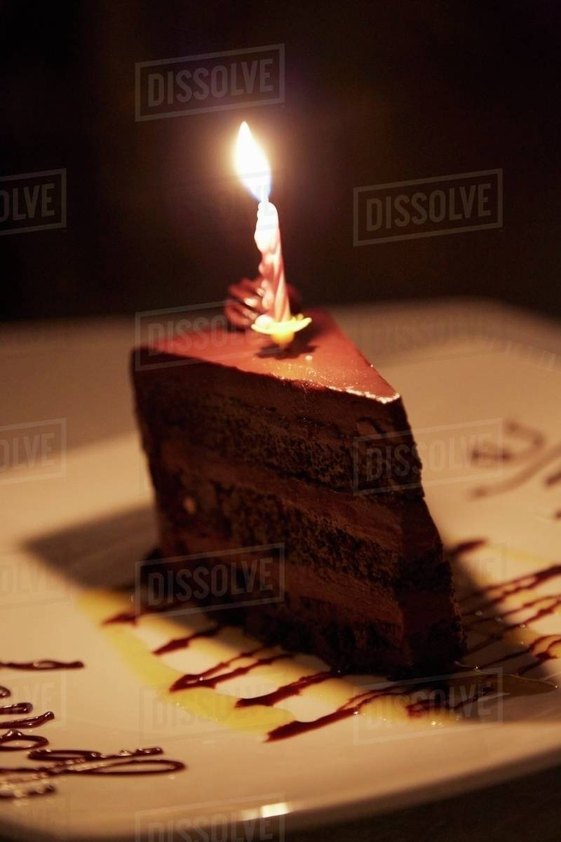 A Slice Of Chocolate Cake With Birthday Candle