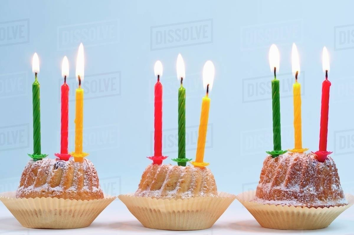 three bundt cakes with lit candles for a birthday stock photo