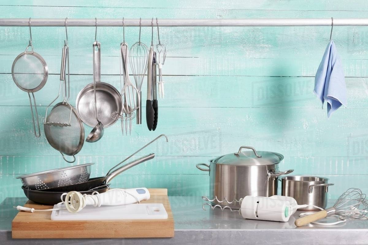 Assorted kitchen utensils on a stainless steel unit and hanging on a ...