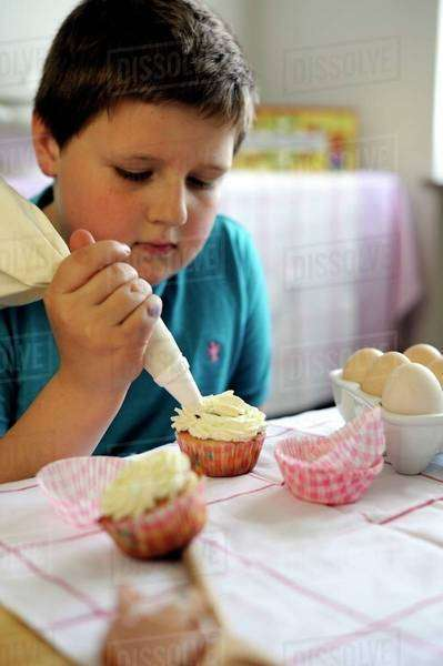 Young boy icing cupcakes Royalty-free stock photo