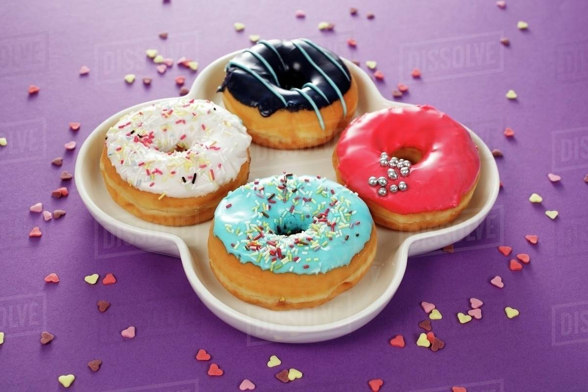 Four doughnuts with colourful glaze and sugar sprinkles stock photo