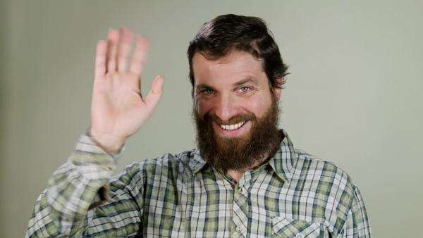 Hipster man says hello in camera on neutral background Royalty-free stock video