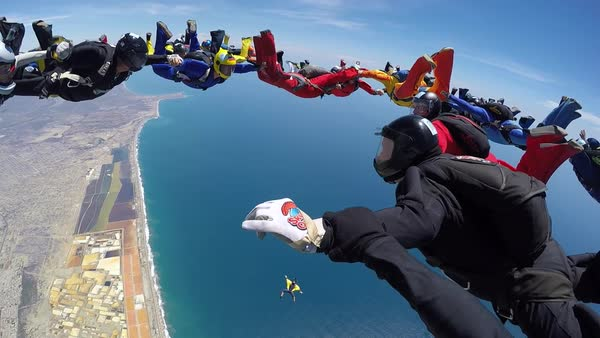 Group of skydivers are hovering in accelerated free fall above coastal city Royalty-free stock video