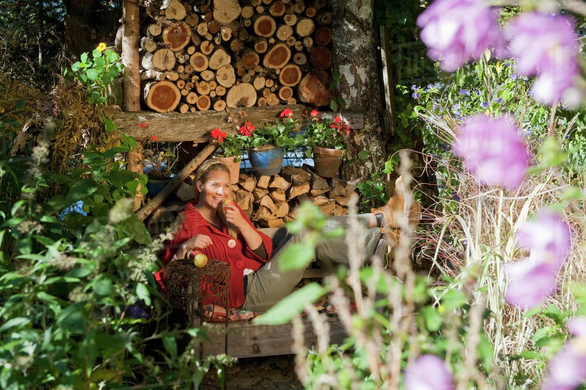 Austria, Salzburg, Flachau, Young woman sitting on bench in farm ...
