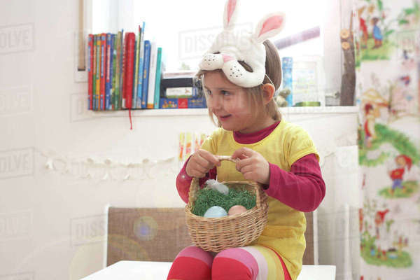 Smiling little girl with Eastern nest and bunny mask Rights-managed stock photo
