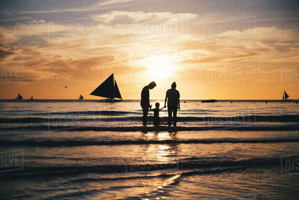 Philippines, Boracay, family with one child at seashore by sunset Rights-managed stock photo