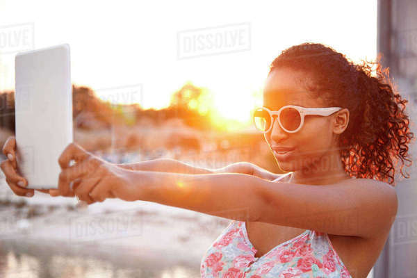 Young woman taking selfie with digital tablet at sunset Rights-managed stock photo