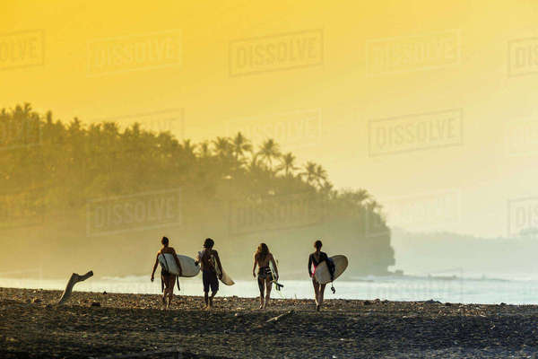 Indonesia, Bali, surfers on beach in the morning light Rights-managed stock photo
