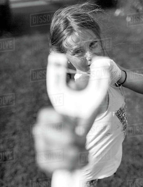 Girl with slingshot pointing at viewer Rights-managed stock photo