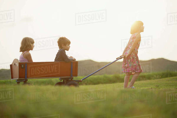 Girl pulling trolley with little boy and girl sitting inside Rights-managed stock photo