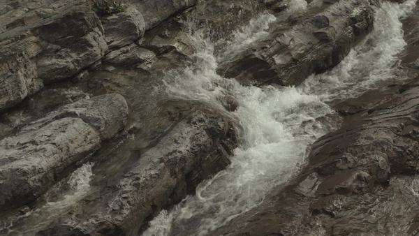 Tilting shot showing water falling down in cascades over a rocky slope Royalty-free stock video