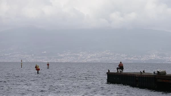 Wide shot of a man fishing on a coast of Sorrento, Italy Royalty-free stock video