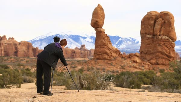 Woman setting up camera on tripod in desert landscape of Arches National Park Royalty-free stock video