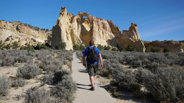 Man walking down trail toward arch in the desert of Utah Royalty-free stock video
