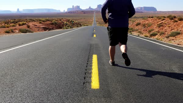 Man running down the road from Forrest Gump Point towards Monument Valley in Utah. Royalty-free stock video
