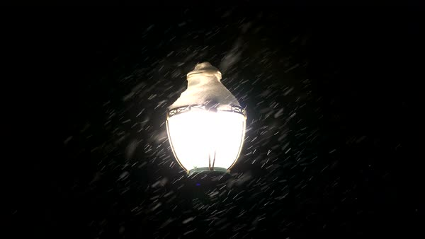 Snow flakes falling in front of street light during winter at night. Royalty-free stock video