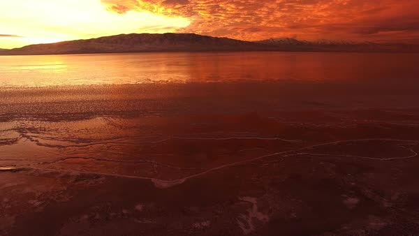 Flying backwards from ice on lake to higher aerial view of colorful sunset over Utah Lake. Royalty-free stock video