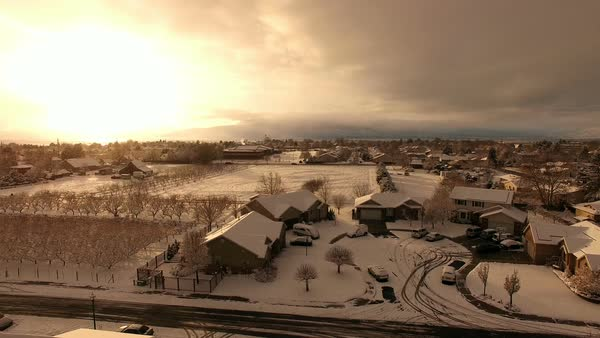 Aerial pan of sunset at snow is falling while flying over neighborhood. Royalty-free stock video