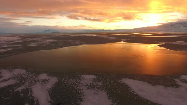 Aerial view flying backwards over frozen lake at sunset as the landscape glows. Royalty-free stock video
