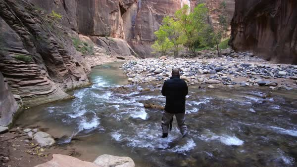 Photographer in river of the Zion Narrows adjusting tripod. Royalty-free stock video